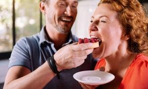 uomo e donna mangiano contenti fetta di pane