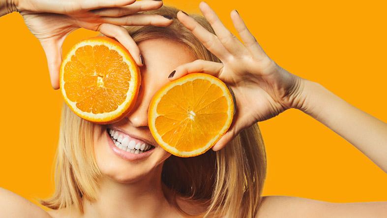 donna sorridente con arance sugli occhi