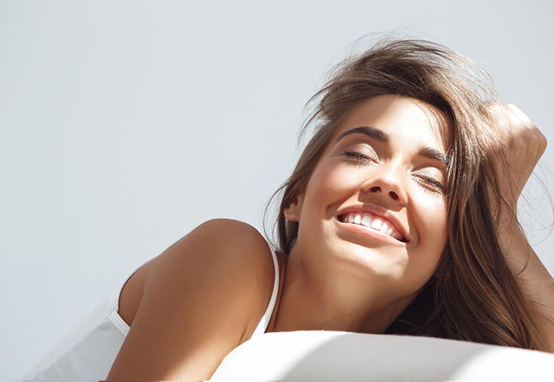 Ragazza sul letto con raggio di sole sul viso